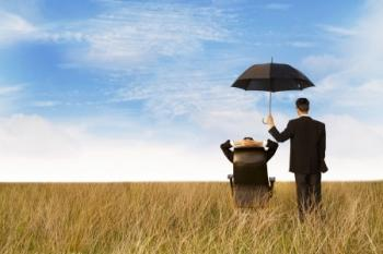 man in field with assistant holding an umbrella over him